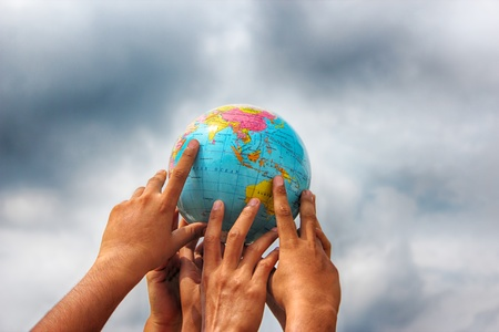hand holding globe: hand holding globe on sky background