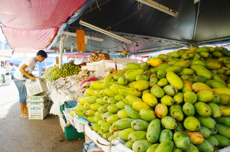 KELANTAN, MALAYSIA-JUN 01: An unidentified local street vendor prepares his fruits stalls street market in Kota Bharu on Jun 01, 2013 in Kelantan, Malaysia. Most of the fruits are imported from Thailand