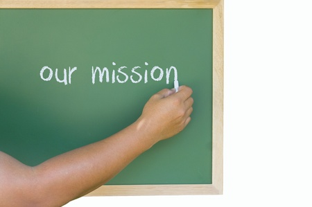 hand writing, our mission on green board Stock Photo