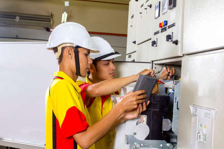 distribution board: two electrician at work on distribution board