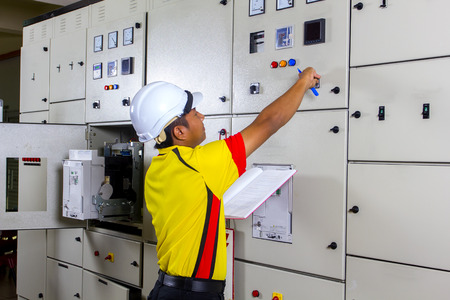 distribution board: young electrician at work on distribution board