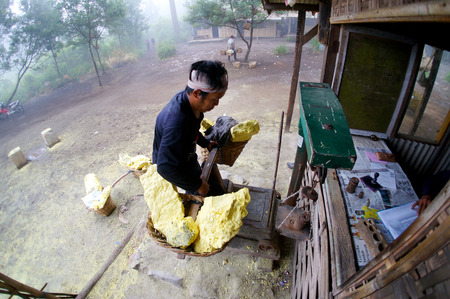 KAWAH IJEN, INDONESIA - APRIL 05: Worker carrying sulfur inside Ijen crater on April 05, 2013. Workers pick up the 60-90kg basket raw sulfur to be weighed.