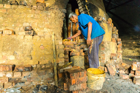 woodburning: TAIPING, MALAYSIA - APRIL 20: Unidentified worker was closing the door to the wood-burning kiln mangrove for processed as charcoal from a cone April 20, 2015 in Taiping, Malaysia. This product for local market and export.