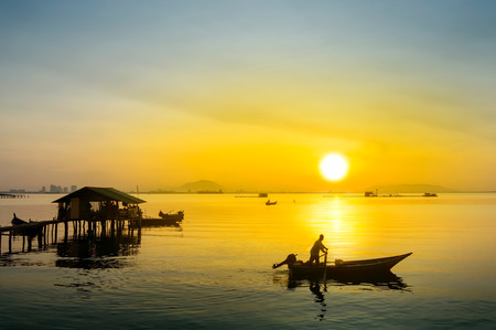 coastal: great sunrise and silhouette traditional fisherman at the beach Stock Photo