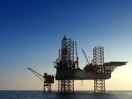 mining ships: silhouette offshore oil rig drilling platform and small ship with blue sky early morning Stock Photo