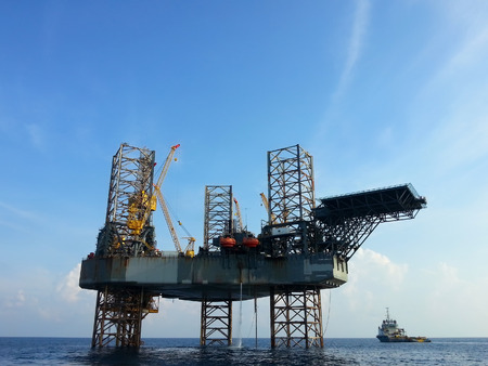 mining ships: offshore oil rig drilling platform and small ship with blue sky