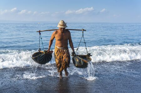 white man: Traditional salt farmer at kusambar bali island, indonesia