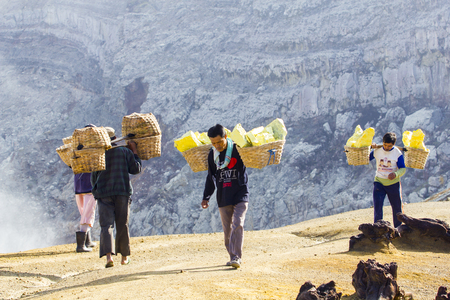 erupt: KAWAH IJEN, INDONESIA - APRIL 7: Unidentified people miner carry baskets with sulfur from the sulfur mines in the crater of the active volcano of Kawah Ijen on April 7, 2014 in East Java, Indonesia Editorial