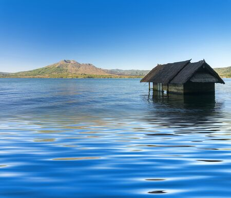sunk: old house sunk in batur lake with batur mount background Stock Photo