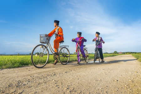 three boy cycling in paddy field during blue sky