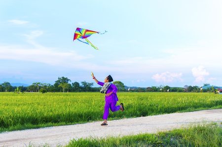 paddies: boy playing colorful kite in a paddy field Stock Photo