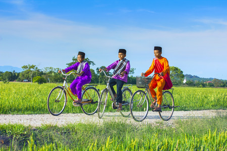 muslim: three boy cycling in paddy field during blue sky