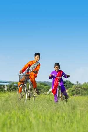 two boy cycling on paddy field during blue sky Stock Photo