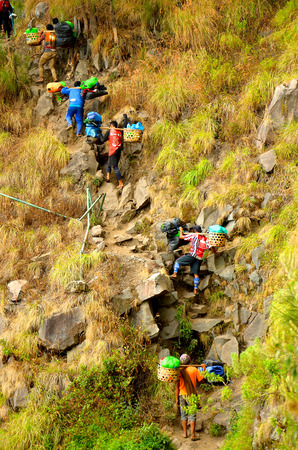 necessities: RINJANI MOUNTAIN, LOMBOK, INDONESIA-SEPT 18, 2016: Unidentified mountain porter carries food necessities walks slowly on trekking path on Plawangan Senaru to Rinjani Mountain in Lombok, Indonesia.