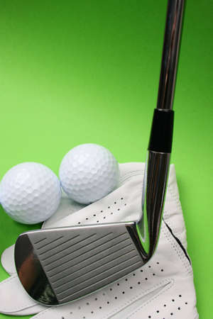 Golf glove, club and balls on a green background photo