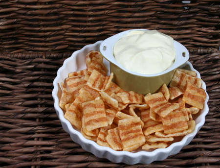 crackles: Chips in a white bowl with dip in a green bowl
