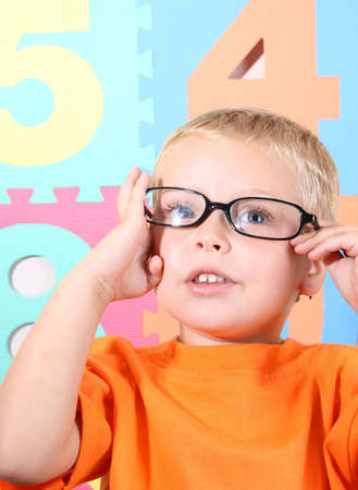 tiny lenses: Blond toddler playing with adult black-rimmed glasses