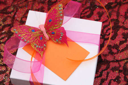 Pink butterfly on a white gift box as a decoration photo