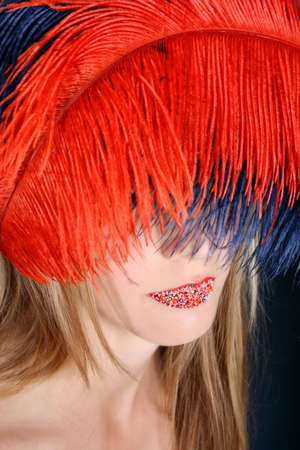 hundreds and thousands: Female model with feathers and hundreds and thousands on her lips.