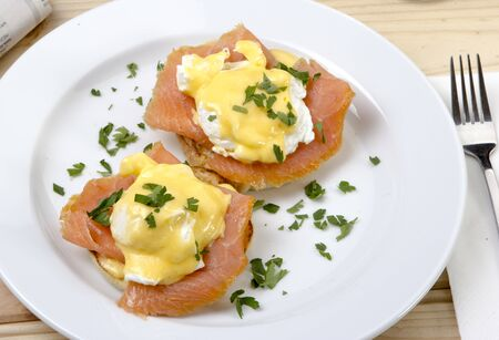 unbroken: Making eggs benedict requires careful orchestration  You have to have warm, smoked solmon, hot buttered toasted English muffins, smoked solmon to your desire, and a warm, creamy, unbroken Hollandaise sauce, all at about the same time Stock Photo