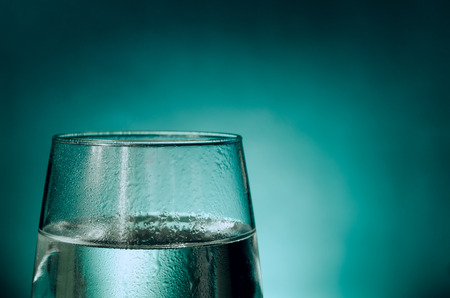 A glass of fresh water dripping with water isolated on an aqua background. Good composition for text addition, simple and clear.