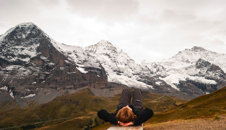 Carefree happy woman lying in front of mountain