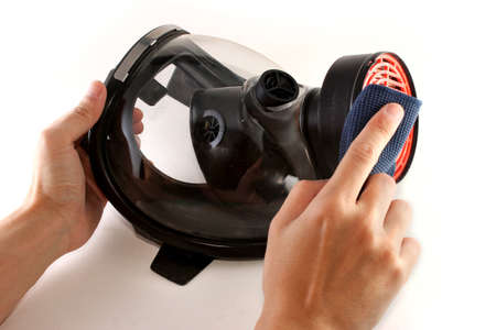 Hands cleaning a black gas mask with a piece of blue cloth photo