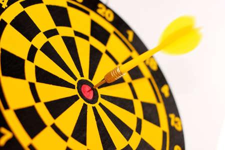 A yellow dart on a bulls-eye