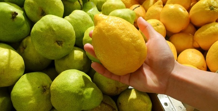 A hand holding a lemon in front of lemons and pears at fruit stall