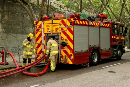 HONG KONG - May 02: Firemen connecting hosepipes to the fire engine on May 02, 2011 in Chai Wan, Hong Kong, China. A 19-year-old woman died and three people were injured in the fire.
