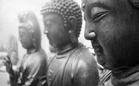 Statues of Ancient gods buddha and Avalokitasvara stand three abreast in temple Stock Photo