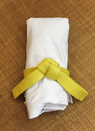 Martial Arts uniform with yellow belt on Tatami Stock Photo