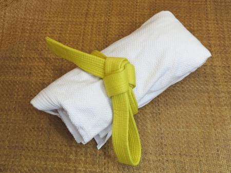 Martial Arts uniform with yellow belt on Tatami Stock Photo