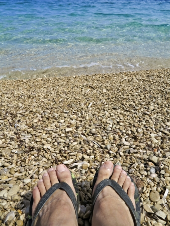 Feet in slippers on a beautiful pebble beach