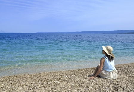 Girl on a pebble beach with hat and sun glasses