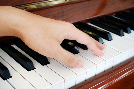 A hand of a performer on the playing piano
