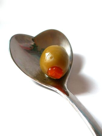 green olive on a spoon