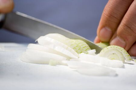A detail image of a man cutting an white young onion