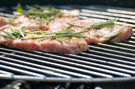 steaks with seasonings on barbecue grill