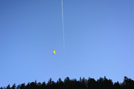 contrail: Parachute over a forest silhouette in a clear sky with plane contrail, Swiss Alps
