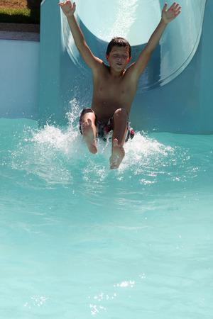tobogan agua: un muchacho de deslizamiento en un tobog�n Foto de archivo
