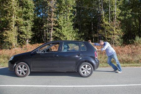 彼の車を押す 写真素材