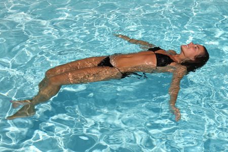 girl floating in a swimming pool photo