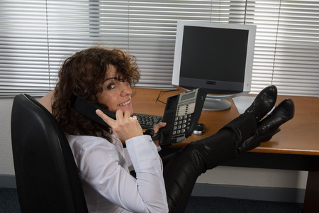 Image of relaxed business woman kepping hands behind head photo