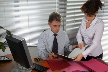 senior and a secretary discuss something during their meeting, photo