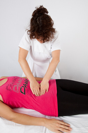 practitioner: Woman lying while being massaged by her practitioner indoors