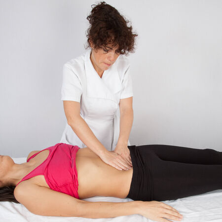 massaged: Woman lying while being massaged by her practitioner indoors