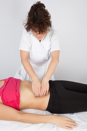 lower limb: Woman lying while being massaged by her practitioner indoors