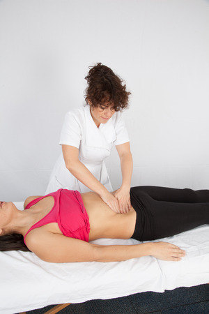 kneecap: Woman lying while being massaged by her practitioner indoors