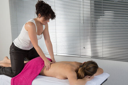 recovery position: Woman lying on mat receiving massage from thai therapist